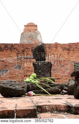 Incomplete Of Ancient Stone Buddha With Lotus Flower On The Lap In The Ruins And Ancient Remains At