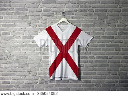 Alabama Flag On Shirt And Hanging On The Wall With Brick Pattern Wallpaper. The States Of America,