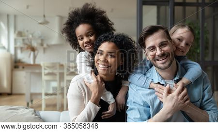 Happy Multiracial Couple Enjoying Sweet Family Moment With Children.