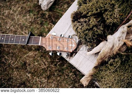 Guitar Fretboard And Headstock On Green Grass In Nature.