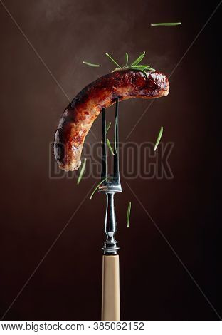 Grilled Sausage With Rosemary. Hot Sausage On A Fork Sprinkled With Rosemary.