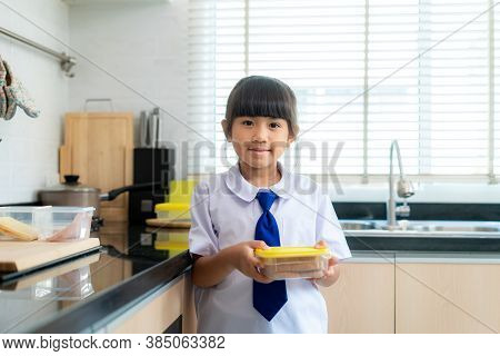 Asian Elementary School Student Girl In Uniform Making Sandwich For Lunch Box In Morning School Rout