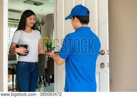 Asian Delivery Young Man In Blue Uniform Smile And Holding Food Boxes In Front House And Asian Woman
