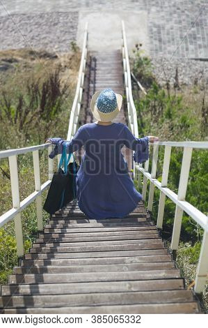 Vertical Shot Of A Woman  Carefully Descending On A Staircase Down The Hill
