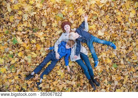 Mother And Two Children Lies On Yellow Leaves In Park. Family Having Fun In Forest. Top View