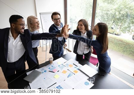 Overjoyed Diverse Coworkers Participate In Teambuilding Activity