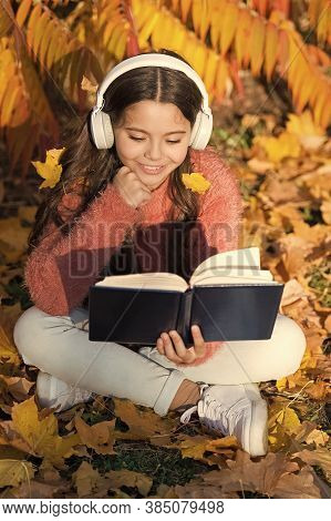 Activate Listening. Small Child In Headphones Practice Listening Comprehension. Little Girl Read Boo