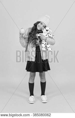 Stay Childish. Small Child Hold Soft Toy And Apple. Little Girl Enjoy School Break Yellow Background