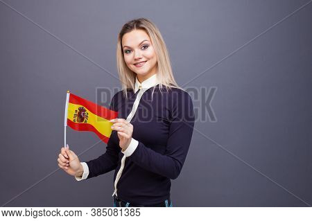 Immigration And The Study Of Foreign Languages, Concept. A Young Smiling Woman With A Spain Flag In