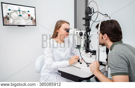 Eye Doctor Woman Is Doing A Diagnostic Vision Exam Adult Man. Eye Exam And Diagnostic Eye Diseases