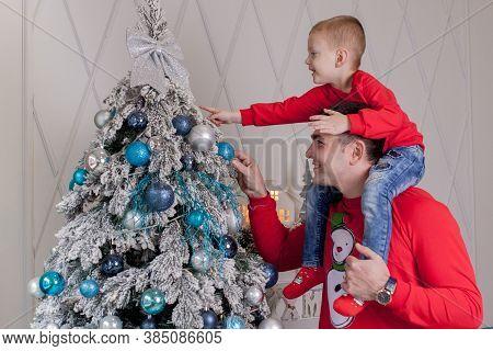 Happy Father And Son Enjoying Decorating Christmas Tree With Christmas Balls And Light Garland Prepa