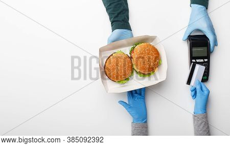 Courier Delivered Box With Hamburger And Cheeseburger To Home. Customer In Rubber Gloves Pay By Cred