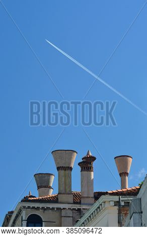 An Airplane Has Left A White Vapour Trail In A Clear Blue Sky. Below Is A Cluster Of Chimneys On A R