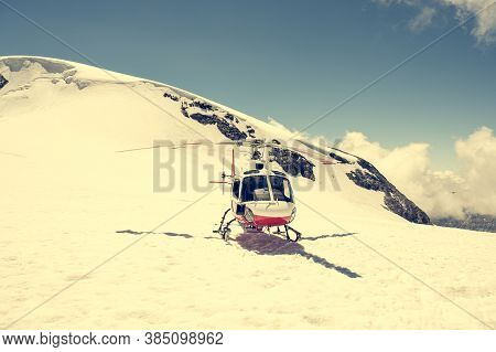 White And Red Helicopter Landed On Snow In Winter.