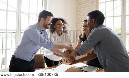 Overjoyed Multicultural Coworkers Stack Hands Engaged In Teambuilding