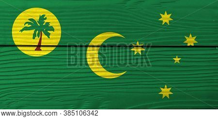 Flag Of Cocos (keeling) Islands On Wooden Wall Background. Grunge Cocos Flag Texture, A Palm Tree On