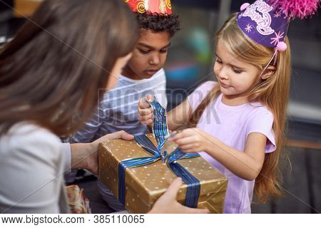 caucasian girl unwrapping birthday present from young adult female brunette with afro-american cute little boy watching