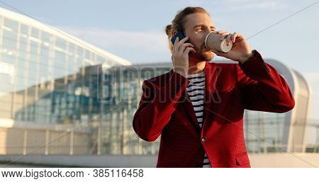 Casual Happy Handsome Male In Red Jacket Standing Outdoor, Sipping Hot Drink And Talking On Cellphon