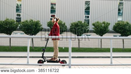 Caucasian Stylish Young Man In Headphones Riding Electric Scooter And Standing Still On Street In Ci