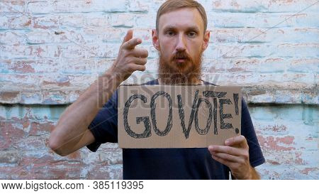 Man Shows Cardboard With Go Vote Sign On Brick Wall Urban Background. Voting Concept. Make The Polit