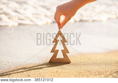 Female Hand Holding Timber Wooden Christmas Tree On A Sand On A Tropical Beach Near Ocean, Summer Ch