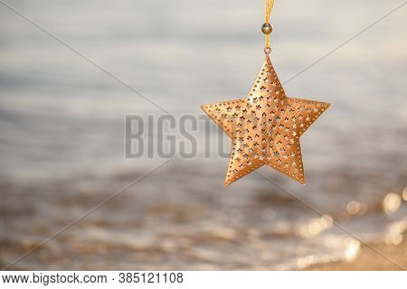 Christmas Gold Star Decoration On The Beach On A Seascape Backgound, Summer Christmas And Winter Hol