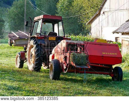 Zetea, Romania- 13 September 2020: Old Tractor Equipped With Welger Baling Press In The Early Hours.