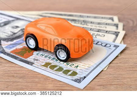 Orange Toy Car On Few 100 Dollar Banknotes. Concept Of Car Buying, Renting, Service, Repair And Insu