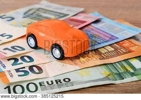 Orange Toy Car On Different Euro Banknotes. Concept Of Car Buying, Renting, Service, Repair And Insu