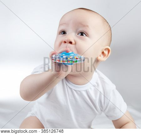 Photo Of A Ten-month-old Baby With Blue Rattle In Mouth