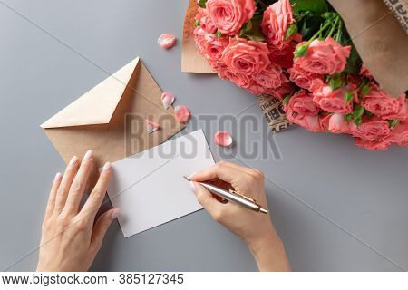 Woman Writing Greeting Card On Gray Table With Bouquet Of Pink Roses. Writing Letter Concept. Top Vi