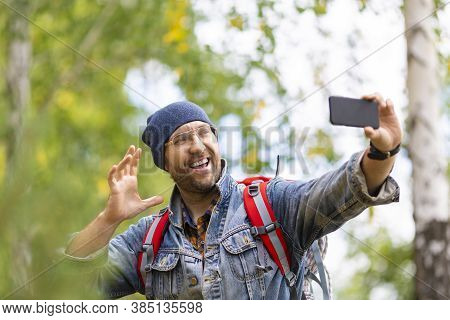 Male Hiker Make A Selfie Or Having A Video-call With Mobile Phone. Man Trekker Taking A Photo.