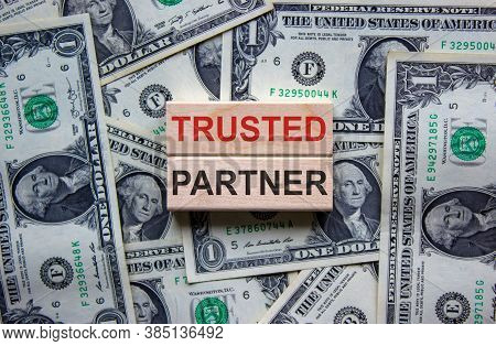 Concept Words 'trusted Partner' On Wooden Blocks On A Beautiful Background From Dollar Bills. Busine