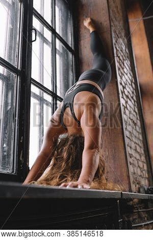 Strong Female Make Yoga Exercises On Windowsill In Loft Class, One-legged Down Dog, Eka Pada Adho Mu