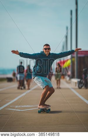 Happy Carefree Skater In A Hoodie And Sunglasses Rides A Longboard. Summer Fun Activities Concept.