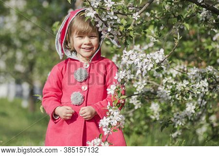 Smiling Cute Little Girl In Red Coat Is Standing Outdoors With Blooming Branch.