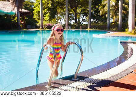Child In Swimming Pool With Ball. Kids Swim.