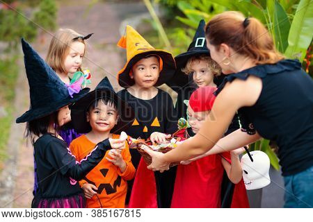 Kids Trick Or Treat On Halloween Night. Mixed Race Asian And Caucasian Children At Decorated House D
