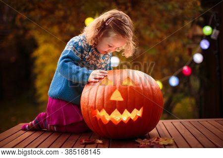 Little Girl Carving Pumpkin At Halloween. Dressed Up Child Trick Or Treating. Kids Trick Or Treat.