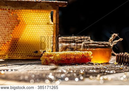 Honey In Glass Bowl, Wooden Honey Dipper And Honeycombs With Honey On Wooden Table On Background Hon