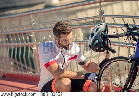 Male Cyclist Crouched Near A Bicycle Wheel