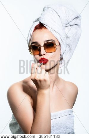 Fashion blogger at the morning. Young glam pretty woman with towel and sun glasses makes make-up with red lipstick looking at camear like at mirror