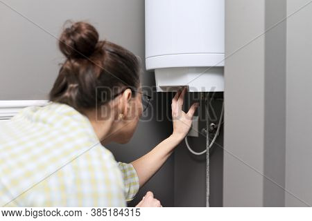 Home Water Heater, A Woman Regulates The Temperature On An Electric Water Heater, Comfort And Hot Wa