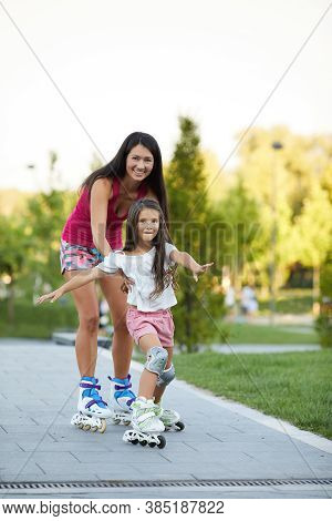 Smiling Mother Is Teaching Her Little Daughter To Skate On Roller Skating In Summer Park