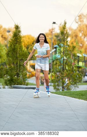 Happy Young Woman Is Rollerskating In Summer Park.