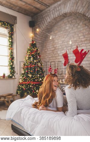 Couple In Love Wearing Pajamas And Deer Antlers Costume Lying In Bed On Christmas Morning, Having Fu