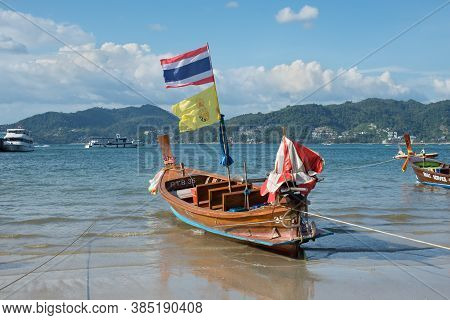 Phuket, Thailand - November 29, 2019: Traditional Longtail Boat With National Flag On The Shore Of P