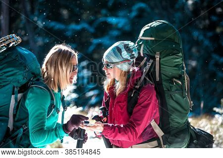 Two Tourists Look At The Phone. Two Friends Travel Together. Women With Backpacks In The Winter Moun