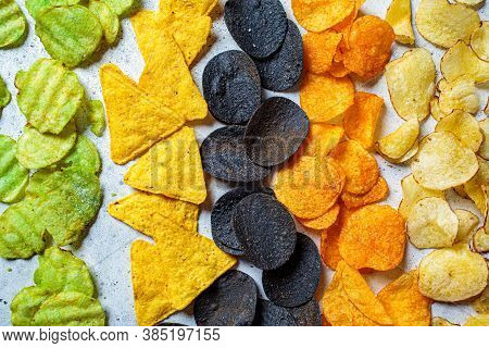 Different Types Of Colored Potato Chips, Gray Background. Fast Food Concept, Unhealthy Fatty Carbohy