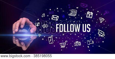 hand holding wireless peripheral with FOLLOW US inscription, social media concept